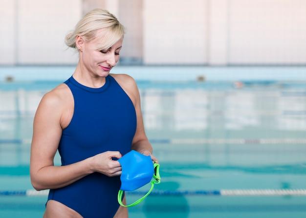 Blonde swimmer holding swimming cap Free Photo