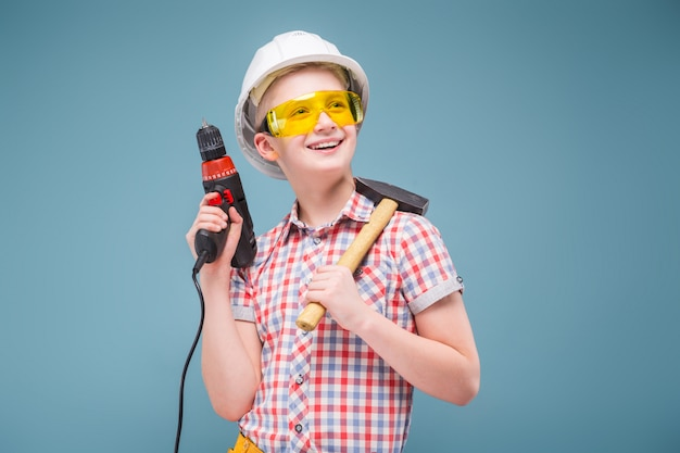 Blonde teenager blonde in the construction helmet with a screwdriver and hammer Premium Photo