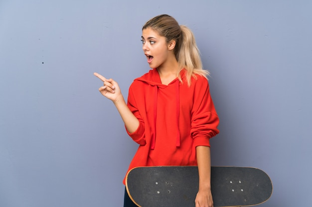 Blonde teenager skater girl over grey wall surprised and pointing side Premium Photo