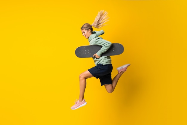 Blonde teenager skater girl jumping  on yellow Premium Photo