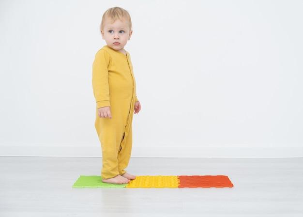 整形外科マットの上に立っている金髪の幼児 Premium写真