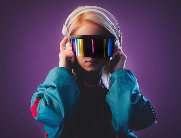 Blonde in vr glasses and headphones on pink wall Premium Photo