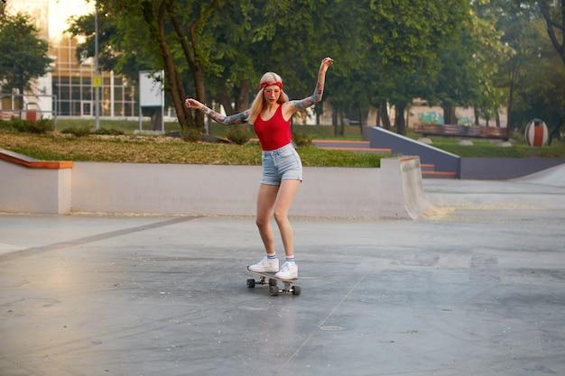 Блондинка с татуированными руками, одетая в красную футболку и джинсовые шорты с вязаной банданой на голове, в красных очках, наслаждается лонгбордингом в скейт-парке, выглядит сосредоточенно с поднятыми руками. Бесплатные Фотографии