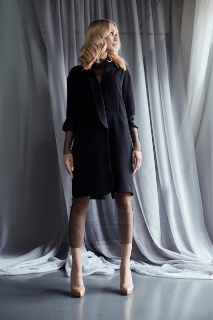 Blonde woman in a black autumn coat stands Premium Photo