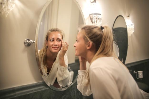 Красивая блондинка любуется собой в зеркале