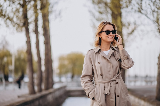 Blonde woman in coat outside in park Free Photo