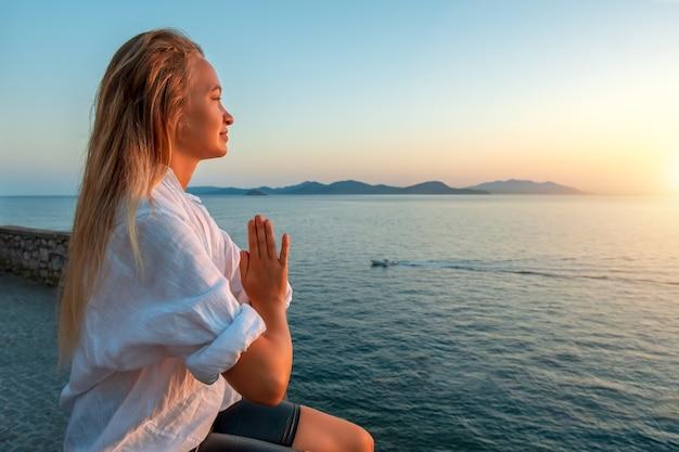 Блондинка делает дыхательные упражнения пранаямы на закате на море. . Premium Фотографии