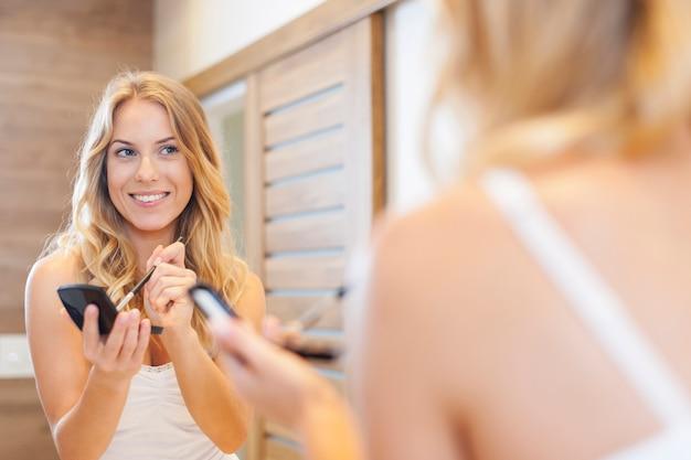 鏡の前で化粧をしているブロンドの女性 無料写真