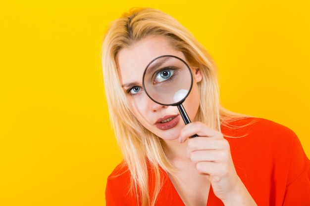 Blonde woman in dress with magnifying glass Premium Photo