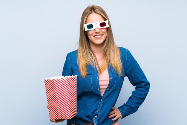 Blonde woman eating popcorns posing with arms at hip Premium Photo