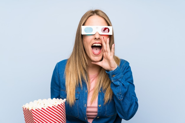 Blonde woman eating popcorns shouting with mouth wide open Premium Photo