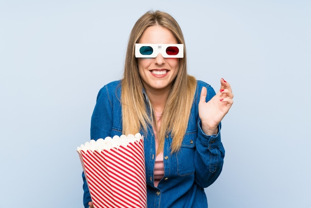 Blonde woman eating popcorns unhappy and frustrated with something. negative facial expression Premium Photo