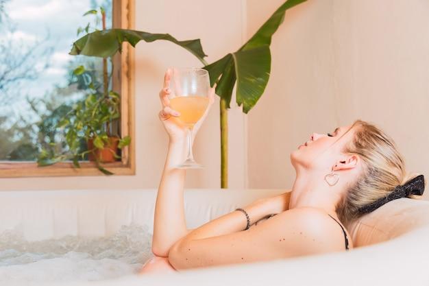 ジャグジーでお風呂を楽しんでいる金髪の女性。ジェットバスでワインのグラスと横になっている若い女性。人、美容、スパ、健康的なライフスタイルとリラクゼーションのコンセプト。 Premium写真