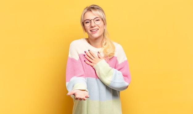 幸せと恋を感じ、片方の手で心の横に、もう片方の手で前に伸ばして笑っている金髪の女性 Premium写真