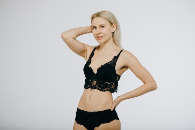 금발 여자 행복 미소 검은 란제리, 브래지어와 팬티에 착용 포즈. 프리미엄 사진