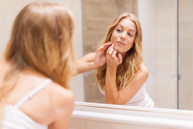 La donna bionda ha problemi con la pelle del viso Foto Gratuite