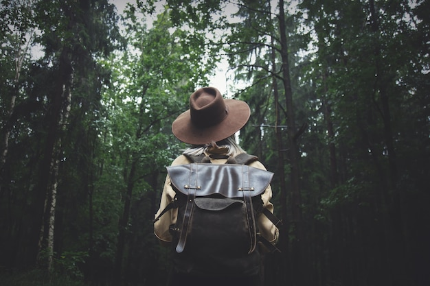 Blonde woman in hat with backpack in rainy day in forest Premium Photo