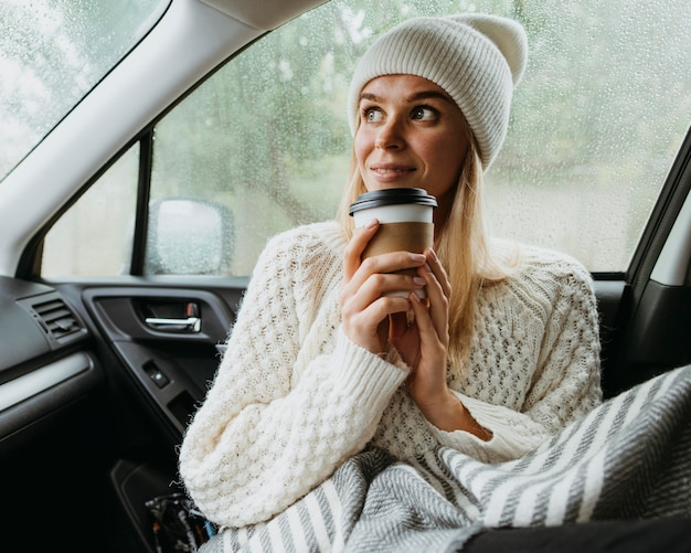 車の中で一杯のコーヒーを保持しているブロンドの女性 無料写真