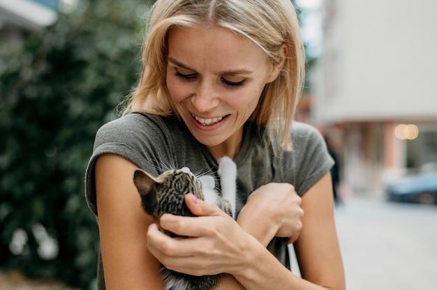 Блондинка женщина держит милый маленький кот Premium Фотографии