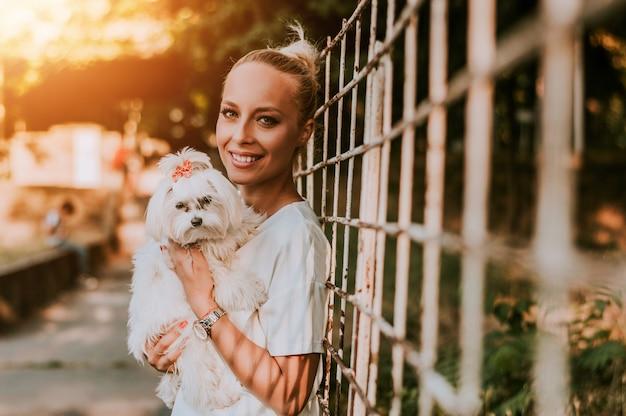 Blonde woman holding her maltese dog. Premium Photo