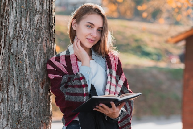 Blonde woman holding a notebook and looking at photographer Free Photo