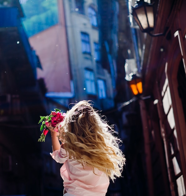 Blonde woman holds a bouquet of pink peonies whirling on the street Free Photo