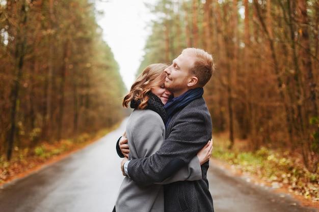 Blonde woman hugging her husband ourtdoors Free Photo