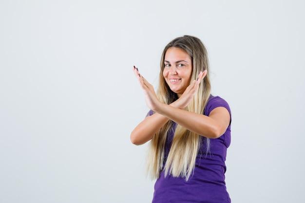 Блондинка в фиолетовой футболке показывает жест стоп и выглядит счастливой, вид спереди. Бесплатные Фотографии