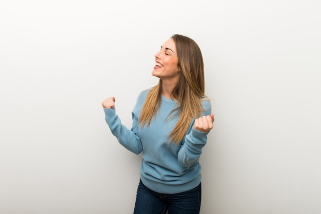 Blonde woman on isolated white background celebrating a victory Premium Photo