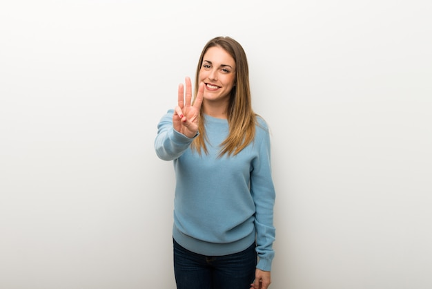 Blonde woman on isolated white background happy and counting three with fingers Premium Photo
