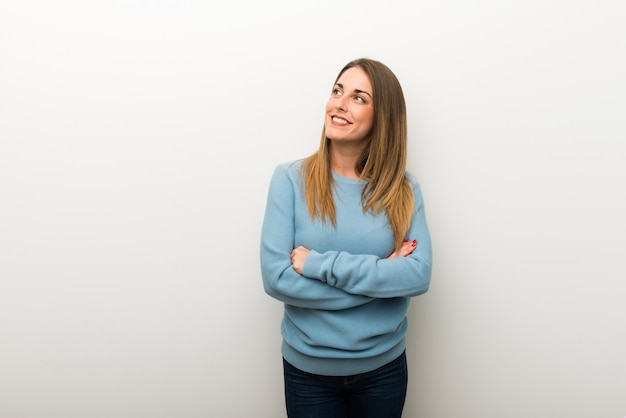 Blonde woman on isolated white background looking up while smiling Premium Photo