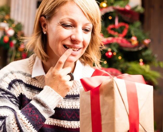 Blonde Woman Opening Christmas Gifts Photo Free Download