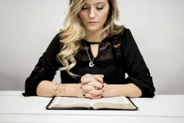 Donna bionda che legge la bibbia e che prega Foto Gratuite