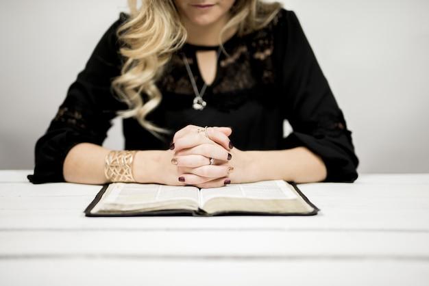 Donna bionda che legge una bibbia sul tavolo Foto Gratuite
