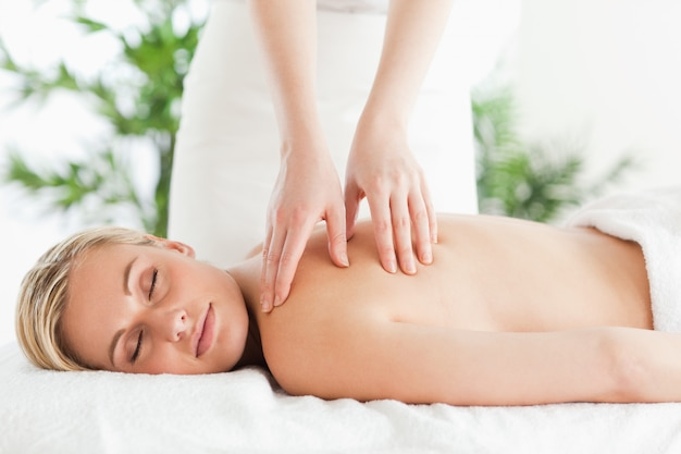 Blonde woman relaxing on a lounger during massage Premium Photo