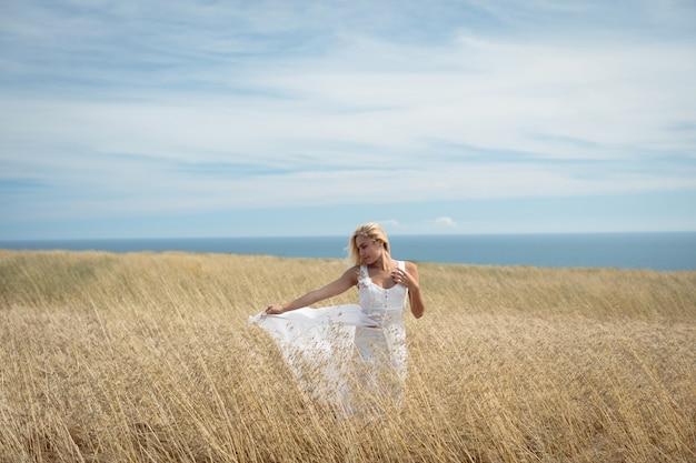 Блондинка стоит в поле Бесплатные Фотографии