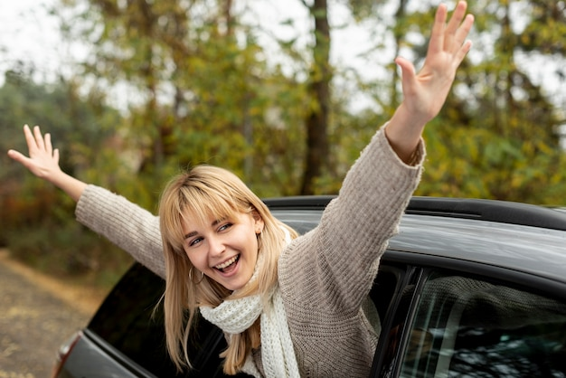 Blonde woman taking her hands out of car Free Photo