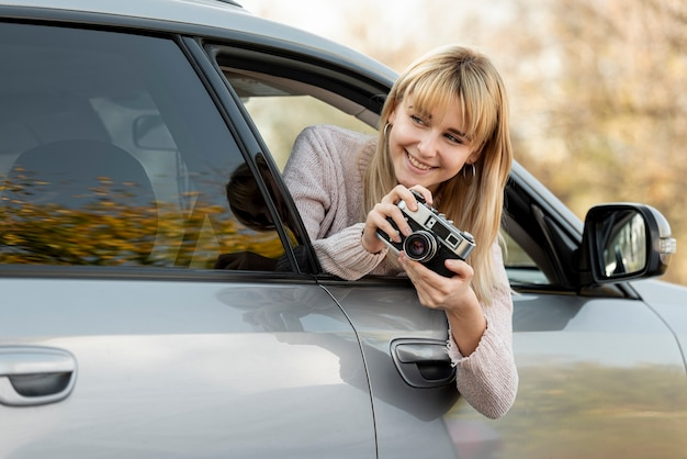 Blonde woman taking pictures from car Free Photo