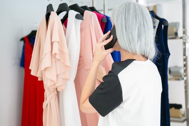 Donna bionda che parla sul telefono cellulare durante la scelta dei vestiti e la navigazione di abiti su rack nel negozio di moda. vista posteriore. cliente boutique o concetto di vendita al dettaglio Foto Gratuite