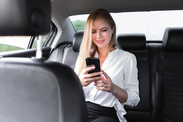 Blonde woman using a phone in the car Free Photo