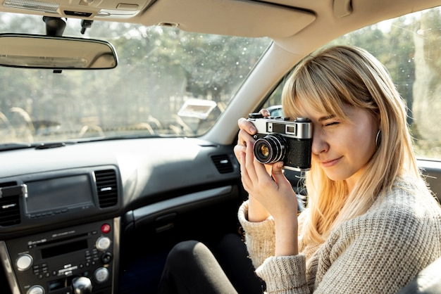 Blonde woman using a vintage camera in car Free Photo