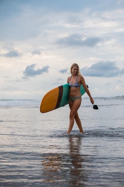 彼女のサーフィンボードとビーチの上を歩く金髪の女性 無料写真