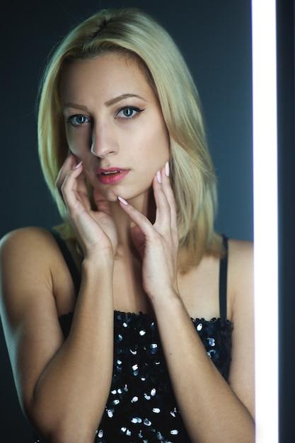 Blonde woman wearing elegant black sequin strap cami dress standing on dark interior Premium Photo