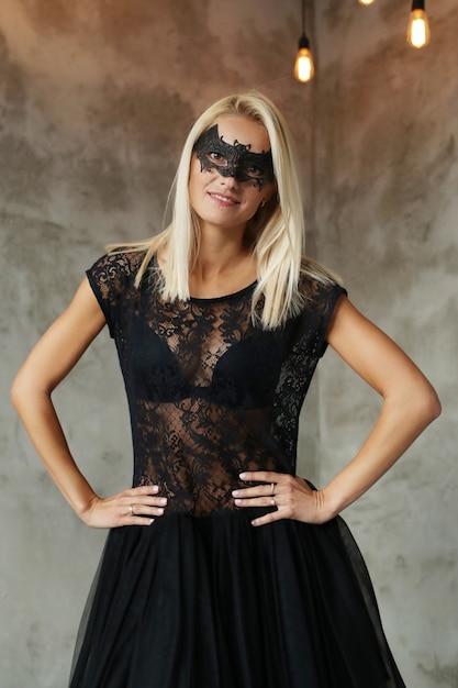 ハロウィーンや仮装パーティー、黒い衣装のコウモリの形のマスクを持つ金髪の女性 無料写真