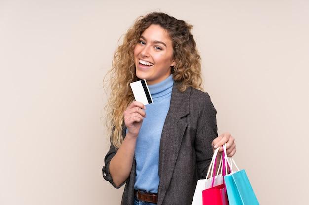 Блондинка с вьющимися волосами, изолированные на бежевом фоне, держит сумки и кредитную карту Premium Фотографии