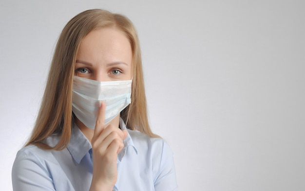 Blonde woman with medical mask shows hush and be quiet gesture Premium Photo