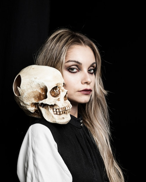 Blonde woman with skull on shoulder Free Photo