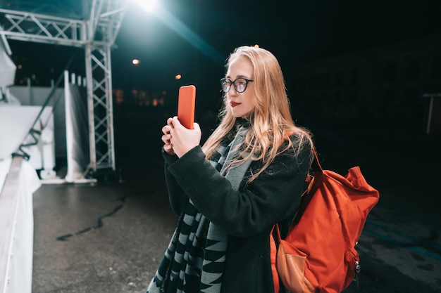 Blonde woman with smartphone at night in the street. Free Photo