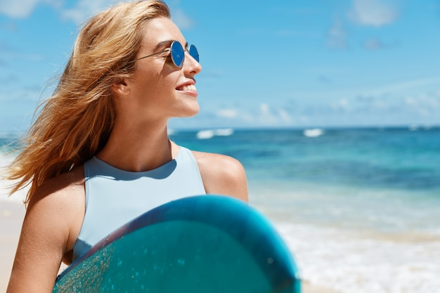Blonde woman with surfboard on beach Free Photo