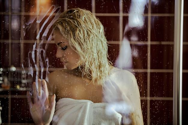 Блондинка у мокрой стены
